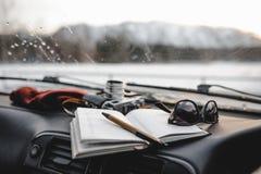 Notizbuch, Gläser und Filmkamera auf dem Armaturenbrett Stockfotografie