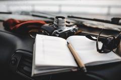 Notizbuch, Gläser und Filmkamera auf dem Armaturenbrett Stockbild