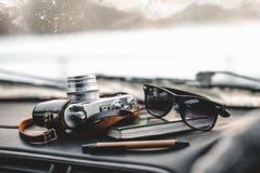 Notizbuch, Gläser und Filmkamera auf dem Armaturenbrett Lizenzfreie Stockfotografie