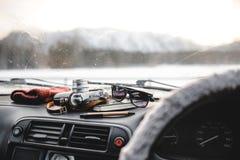 Notizbuch, Gläser und Filmkamera auf dem Armaturenbrett Ansicht vom Fahrersitz Lizenzfreie Stockfotos