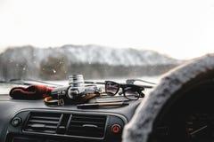 Notizbuch, Gläser und Filmkamera auf dem Armaturenbrett Ansicht vom Fahrersitz Lizenzfreie Stockfotografie