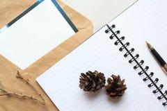 Notizbuch, goldener Stift und Konzert auf dem Schreibtisch, trockene Kegel und Niederlassungen verzierten Tabelle stockfoto