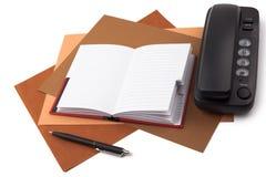 Notizbuch, Kugelschreiber und Telefon auf strukturiertem Papier Stockbilder