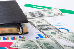 Notizbuch liegt auf Flussdiagrammen und Dollar Lizenzfreie Stockbilder