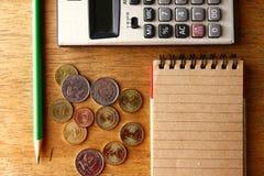 Notizbuch, Münzen, Taschenrechner und Bleistift auf einer Tabelle Lizenzfreie Stockfotografie