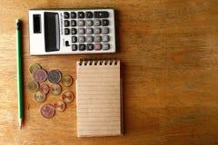 Notizbuch, Münzen, Taschenrechner und Bleistift auf einer Tabelle Lizenzfreie Stockbilder
