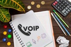 Notizbuch mit Anmerkungen VOIP über den Bürotisch mit Werkzeugen Conce Stockfotografie