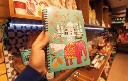 Notizbuch mit Bildern von Indien - Taj Mahal, Kuh, Elefant auf Abdeckung in der Buchhandlung Stockfotografie