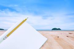 Notizbuch mit Bleistift auf Bretterboden in Meer und Sand einer Strandnatur gestalten landschaftlich Lizenzfreie Stockfotos