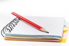 Notizbuch mit Bleistift auf weißem Hintergrund Stockfotografie