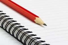 Notizbuch mit Bleistift auf weißem Hintergrund Lizenzfreie Stockfotografie