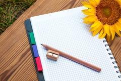 Notizbuch mit Bleistift, Bleistiftspitzer und Sonnenblume Lizenzfreie Stockfotografie