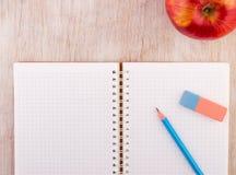 Notizbuch mit Bleistift und Apfel auf Schreibtisch Stockfotos