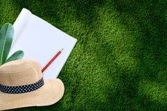 Notizbuch mit Bleistift und Strohhut auf Hintergrund des grünen Grases Lizenzfreies Stockbild