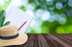 Notizbuch mit Bleistift und Strohhut auf Holztisch mit grünem bokeh Lizenzfreies Stockfoto