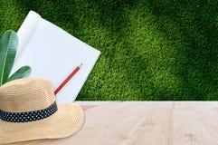 Notizbuch mit Bleistift und Strohhut auf Holztisch mit Hintergrund des grünen Grases Stockfotos