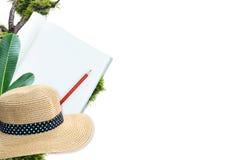 Notizbuch mit Bleistift und Strohhut mit Grün lässt Naturisolat auf Weiß Lizenzfreie Stockbilder