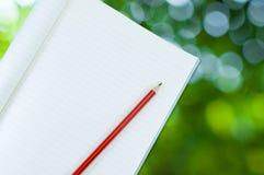 Notizbuch mit Bleistiftisolat auf abstraktem Naturgrün bokeh Hintergrund Lizenzfreies Stockfoto