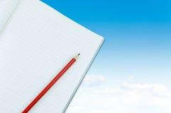 Notizbuch mit Bleistiftisolat auf blauem Himmel mit Wolkenhintergrund Lizenzfreie Stockfotografie