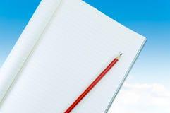 Notizbuch mit Bleistiftisolat auf blauem Himmel mit Wolkenhintergrund Stockfotografie