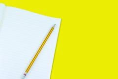 Notizbuch mit Bleistiftisolat auf gelbem Hintergrund Lizenzfreies Stockbild