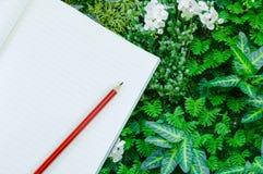 Notizbuch mit Bleistiftisolat auf Grünpflanzenaturhintergrund Lizenzfreies Stockbild