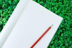 Notizbuch mit Bleistiftisolat auf Grünpflanzenaturhintergrund Stockfotos