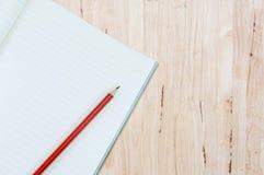 Notizbuch mit Bleistiftisolat auf hölzernem Hintergrund Lizenzfreies Stockbild