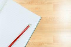 Notizbuch mit Bleistiftisolat auf hölzernem Hintergrund Stockbild