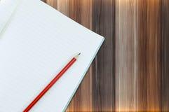 Notizbuch mit Bleistiftisolat auf hölzernem Retro- Hintergrund Lizenzfreie Stockbilder