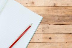 Notizbuch mit Bleistiftisolat auf hölzernem Retro- Hintergrund Stockfotografie