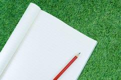 Notizbuch mit Bleistiftisolat auf Hintergrund des grünen Grases Stockfotografie