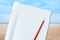 Notizbuch mit Bleistiftisolat auf Meer und Sand an der Natur gestalten Hintergrund landschaftlich Stockfoto