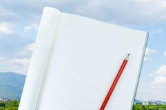 Notizbuch mit Bleistiftisolat auf Stadtlandschaftshintergrund Lizenzfreies Stockfoto