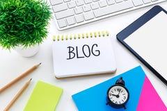 Notizbuch mit Blogwort auf Computertisch Lizenzfreie Stockfotografie