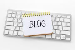 Notizbuch mit Blogwort auf Tastatur Stockfotografie