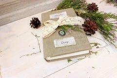 Notizbuch mit dem handgemachten Textilbezug verziert mit Häkelarbeitband und natürlichen immergrünen Anlagen Handwerksthema Stockfotografie