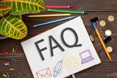 Notizbuch mit einem Anmerkungen FAQ auf dem Bürotisch mit Werkzeugen Concep Stockfotos