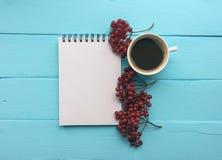 Notizbuch mit einem Frühling, Niederlassung mit Viburnumbeeren und einem Tasse Kaffee Helles Blau, Türkisoberfläche Nahaufnahmeko Stockbild