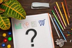 Notizbuch mit einer Anmerkungsfrage über den Bürotisch mit Werkzeugen Lizenzfreie Stockbilder