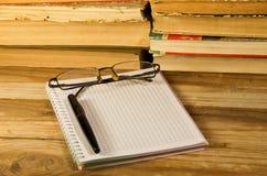 Notizbuch mit Füllfederhalter, Gläsern und Büchern auf hölzernem Schreibtisch Lizenzfreie Stockfotografie