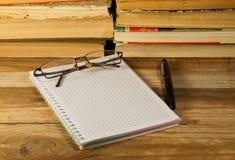 Notizbuch mit Füllfederhalter, Gläsern und Büchern auf hölzernem Schreibtisch Stockfoto