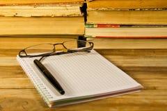 Notizbuch mit Füllfederhalter, Gläsern und Büchern auf hölzernem Schreibtisch Lizenzfreie Stockbilder