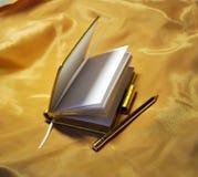 Notizbuch mit Feder auf Gold Stockbild
