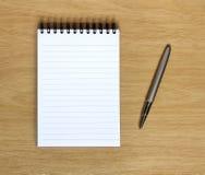 Notizbuch mit Feder auf hölzernem Schreibtisch lizenzfreie stockfotos