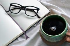 Notizbuch mit Gläsern und einer Tasse Tee im Bett stockfotos