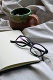Notizbuch mit Gläsern und einer Tasse Tee im Bett lizenzfreie stockfotos