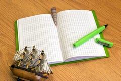 Notizbuch mit grünem Stift und Muscheln Stockbild