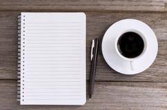 Notizbuch mit Kaffeetasse auf hölzernem Hintergrund Lizenzfreie Stockbilder