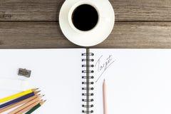 Notizbuch mit Kaffeetasse auf hölzernem Hintergrund Lizenzfreie Stockfotos